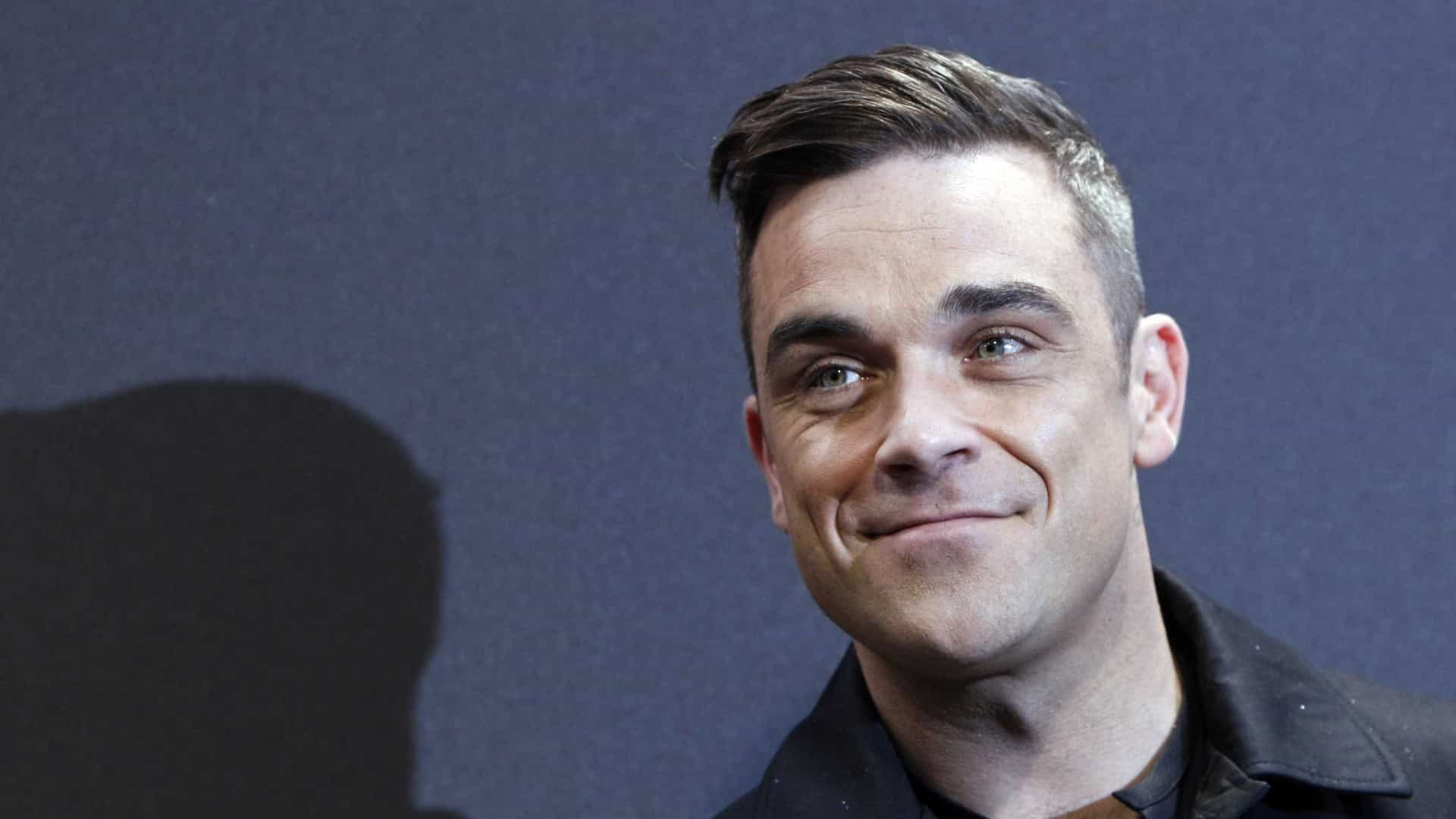 Aos 43 anos, Robbie Williams posa nu para divulgar livro