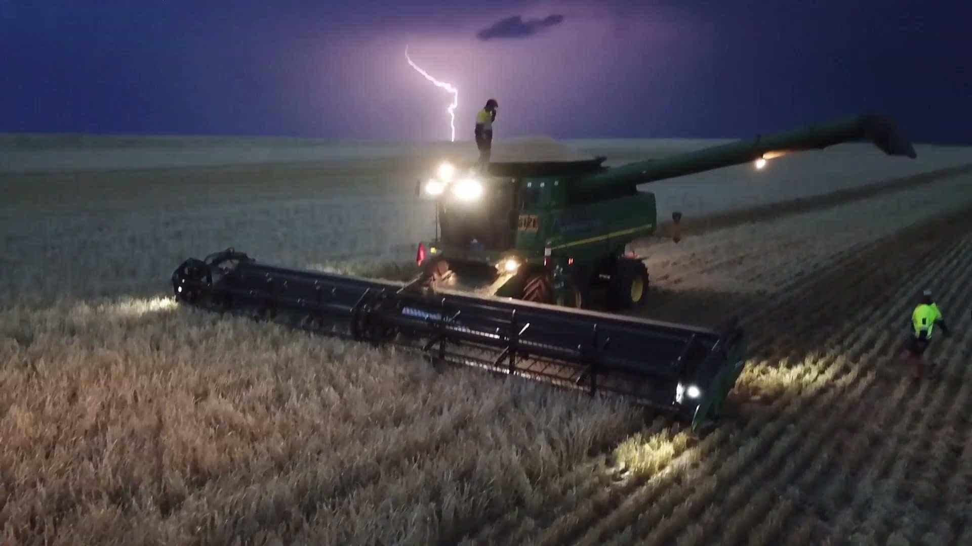 Homem dança em colheitadeira durante tempestade de relâmpagos