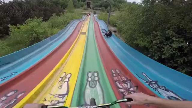 Jovem se aventura de BMX em tobogãs de parques aquáticos abandonados