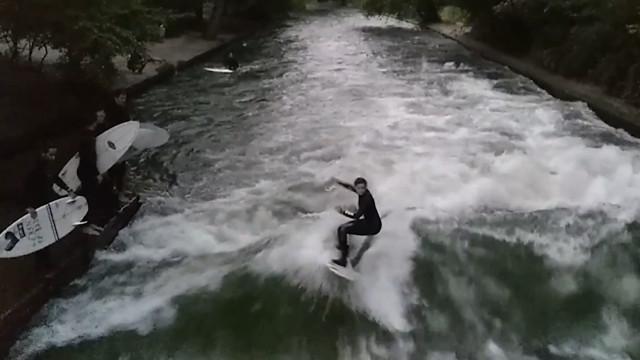 Jovem pratica surf  em um rio de Munique