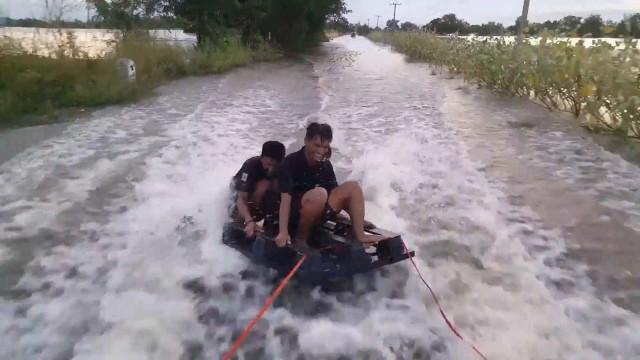 Tailândia: Jovens aproveitam inundações e praticam surf em estrada