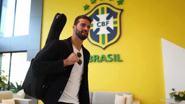 Com violão nas costas, Alisson se apresenta à seleção em Teresópolis