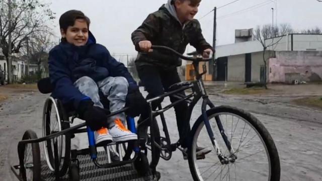 Menino cria bicicleta com sidecar para levar primo em cadeira de rodas